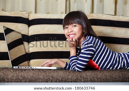 Smiling cute little asian girl with a laptop at home on sofa - stock photo