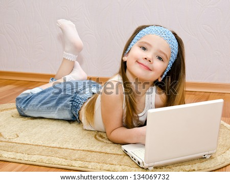 Smiling cute little girl with a laptop at home on the floor - stock photo