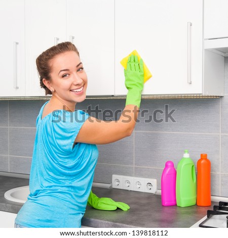 smiling cute woman cleans the kitchen at her home - stock photo