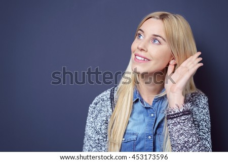 Smiling cute young blond lady in sweater and blue buttoned shirt waving her hand and looking sideways over dark background - stock photo