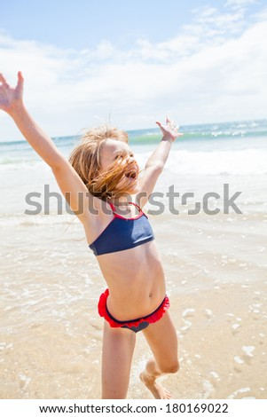 Smiling cute young girl jumping and having fun at beach on sunny day - stock photo