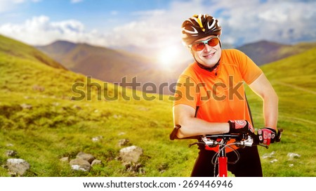 smiling cyclist standing on mountains background collage - stock photo