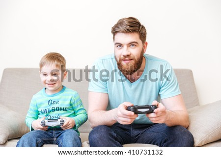 Smiling dad and son sitting and playing computer games on sofa at home - stock photo