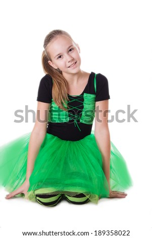 Smiling dancer girl in green tutu skirt sitting isolated on white - stock photo