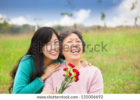 Smiling daughter and her mother with carnation flower on the grass field - stock photo