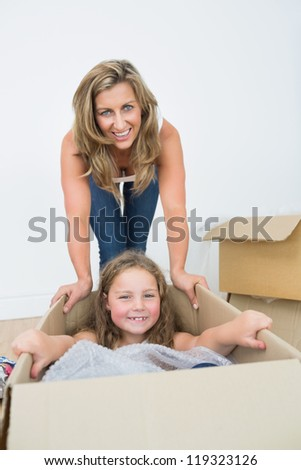 Smiling daughter laying in the box while her smiling mother bows over her - stock photo