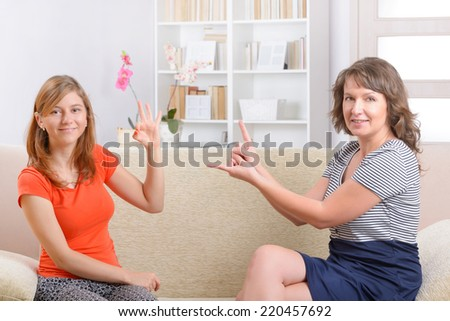 Smiling deaf woman learning sign language and talking with her teacher - stock photo