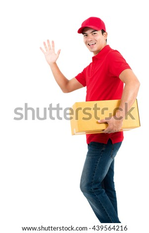 Smiling delivery man making hi (or bye) gesture while holding box in another hand - isolated on white background