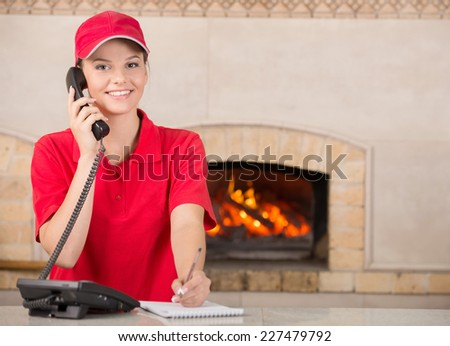 Smiling delivery woman of pizza on the phone. The oven on the background. - stock photo