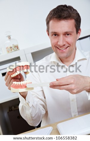 Smiling dentist in office offering tips for brushing teeth with toothbrush - stock photo
