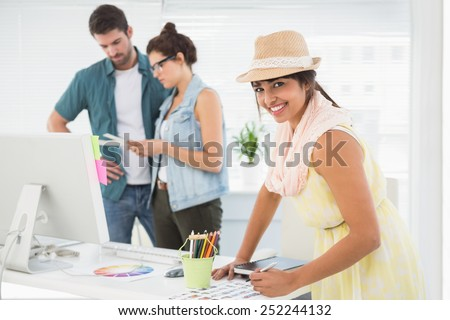 Smiling designer in front of colleagues using colour wheel in the office - stock photo