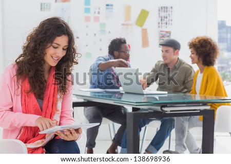 Smiling designer using digital tablet with team at work behind her - stock photo