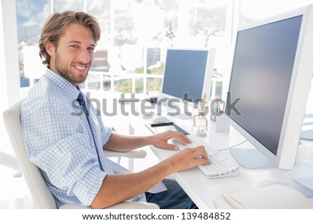 Smiling designer working at his desk in modern office - stock photo