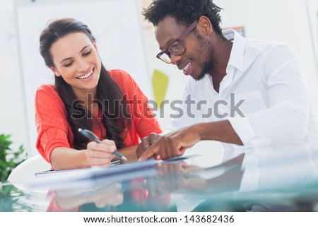 Smiling designers working together at their desk - stock photo