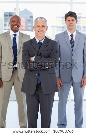 Smiling director standing in front of a relaxed executive and a serious employee - stock photo