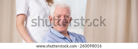 Smiling disabled man and assisting nurse - panorama - stock photo