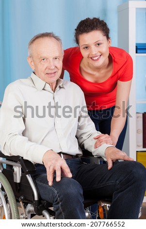 Smiling disabled man and his nurse, vertical - stock photo