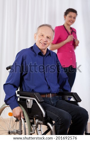 Smiling disabled man and nurse in the background