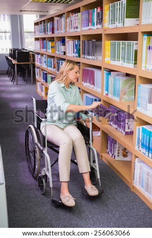 Smiling disabled student in library picking book at the university - stock photo