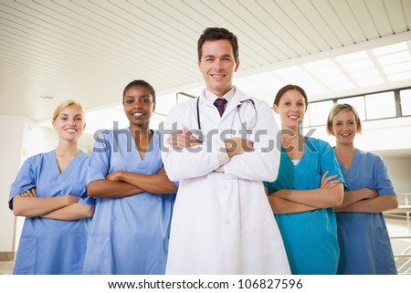 Smiling doctor and nurses with arms crossed in hospital corridor - stock photo