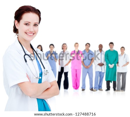 Smiling doctor in front of a team of doctors standing together on a white background