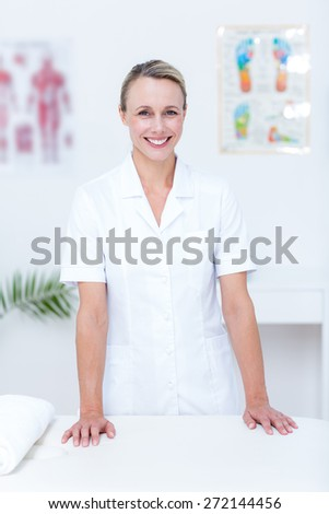 Smiling doctor looking at camera in medical office - stock photo