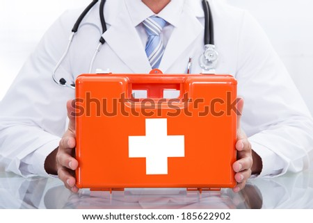Smiling doctor or paramedic in a white lab coat with a stethoscope around his neck holding a red box containing a first aid kit - stock photo