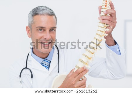 Smiling doctor showing anatomical spine in clinic - stock photo