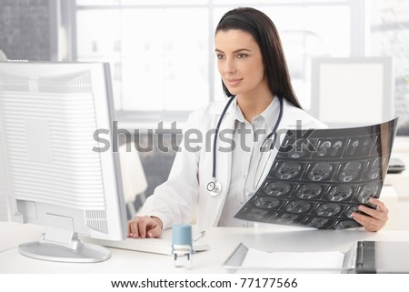 Smiling doctor sitting in office working at desk with computer and xray image.? - stock photo