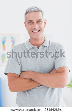 Smiling doctor standing arms crossed and looking at camera in medical office - stock photo