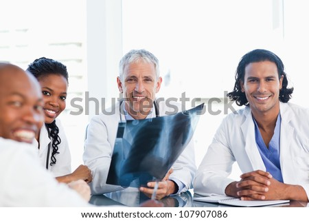 Smiling doctor surrounded by three younger colleagues holding an x-ray of lungs - stock photo