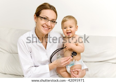 smiling doctor with a happy baby - stock photo