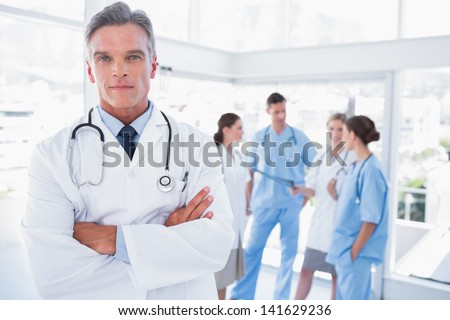 Smiling doctor with arms crossed standing in front of his medical team - stock photo