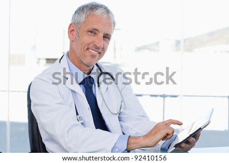 Smiling doctor working with a tablet computer in his office - stock photo