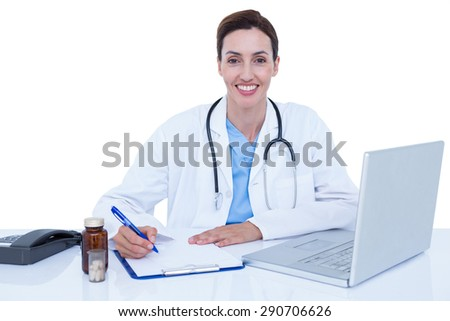 Smiling doctor writing on a notebook - stock photo
