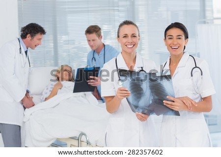 Smiling doctors discussing about patients file in hospital room - stock photo