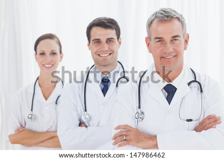Smiling doctors posing together in bright office - stock photo