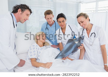 Smiling doctors showing xray to patient in hospital room - stock photo