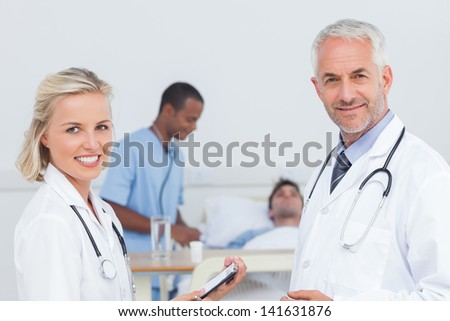 Smiling doctors standing and smiling to the camera in front of patient - stock photo