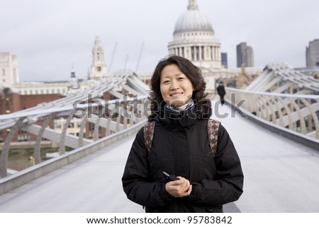 Smiling East Asian Woman at Millennium Bridge, St Paul's Cathedral in the distance. - stock photo