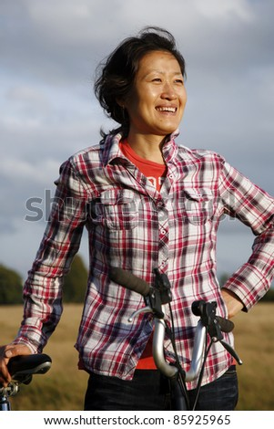 Smiling East Asian Woman in Richmond Park with Bicycle at Dusk - stock photo