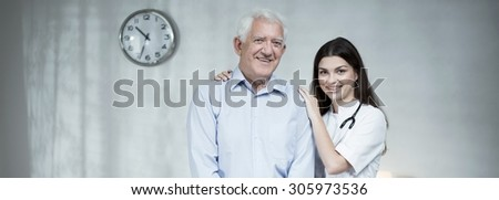 Smiling elder man with female practitioner - panorama - stock photo