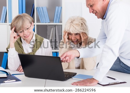 Smiling elder women having problem with computer