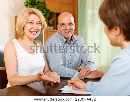 Smiling  elderly  couple discussing details of private insurance with agent - stock photo