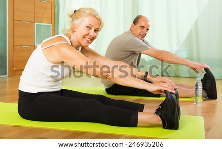 Smiling elderly couple doing morning exercises indoor  - stock photo