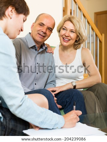 Smiling elderly couple filling questionnaire for employee in the living room at home  - stock photo
