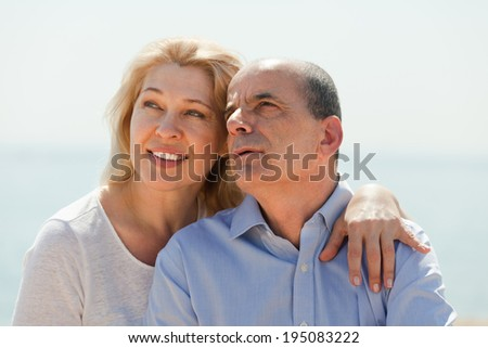 Smiling elderly couple in love at sea shore in warm season