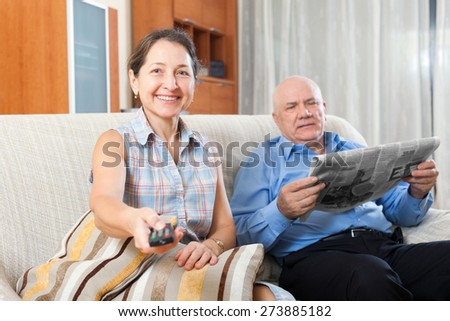 Smiling elderly couple on the couch with the newspaper - stock photo