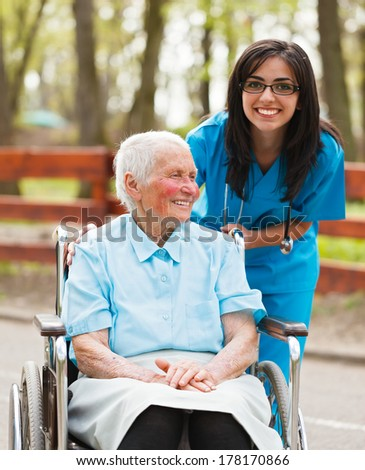 Smiling elderly lady and nurse in park enjoying their time together. - stock photo