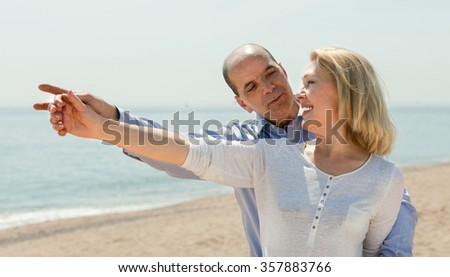 Smiling elderly man showing something to his wife on the beach